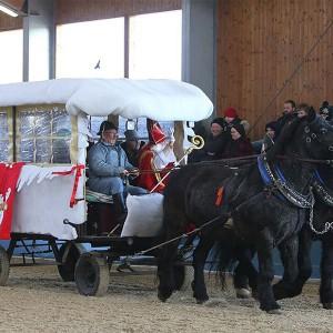 Der Nikolaus auf der weihnachtlich geschmueckten Kutsche begruesse die Zuseher am Bartlgut bei der Nikolausfeier